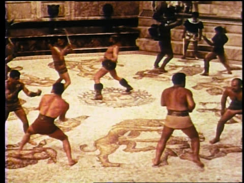 vidéos et rushes de high angle wide shot reenactment roman gladiators fighting with swords + fists in practice - civilisation ancienne