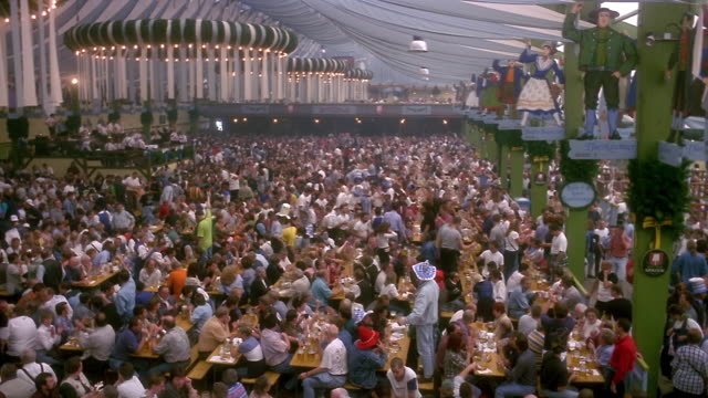 high angle wide shot revelers eating, drinking and dancing in pavilion at oktoberfest / munich, germany - betrunken stock-videos und b-roll-filmmaterial