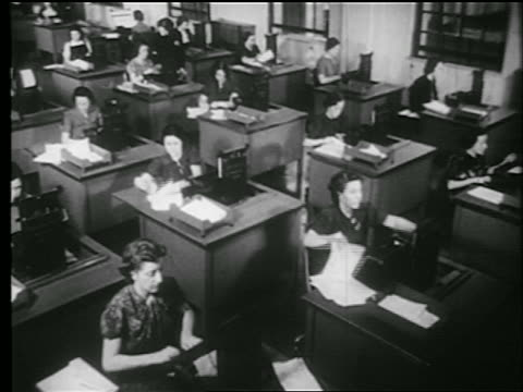 stockvideo's en b-roll-footage met b/w 1939 high angle wide shot rows of women typing on typewriters at desks in office / documentary - 1930