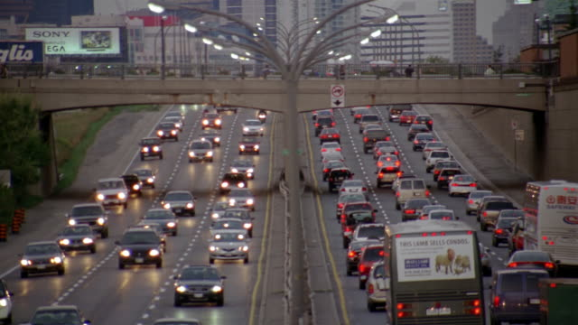 high angle wide shot rush hour traffic on gardiner expressway and pedestrians crossing overpass at dusk / toronto - kelly mason videos stock-videos und b-roll-filmmaterial