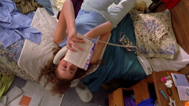 vidéos et rushes de high angle wide shot teen girl lying on messy bed and reading magazine while talking on telephone - messy bedroom