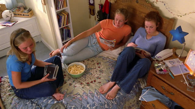 high angle wide shot three teen girls sitting on bed, eating snacks, reading magazines and listening to cds - crisps stock videos & royalty-free footage