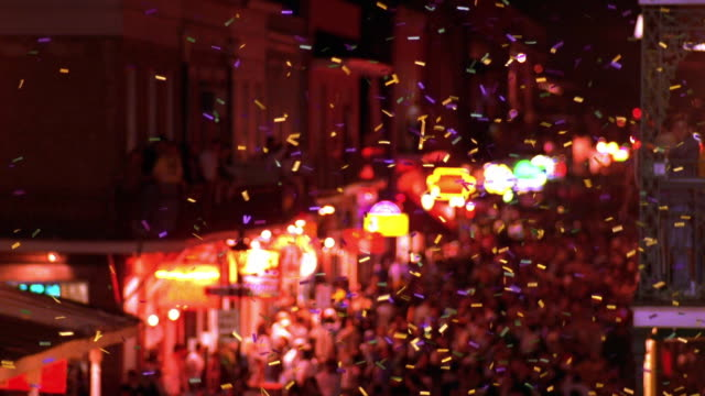 high angle wide shot tilt down confetti falls over crowds of people celebrating mardi gras on bourbon street / new orleans - street party stock videos & royalty-free footage