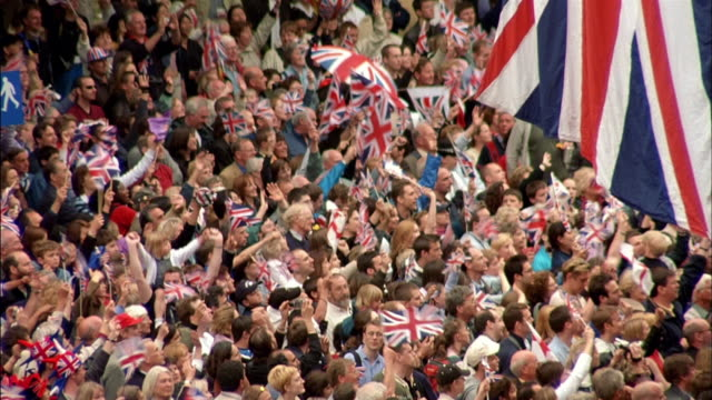 high angle wide shot tilt down crowd waving union flags under large union flag - union jack stock videos & royalty-free footage