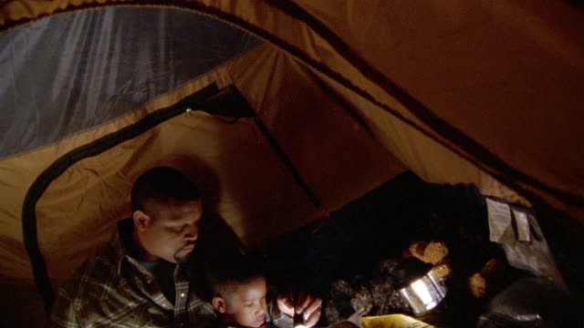 high angle wide shot tilt down father reading book to son inside tent at night - flashlight stock videos & royalty-free footage