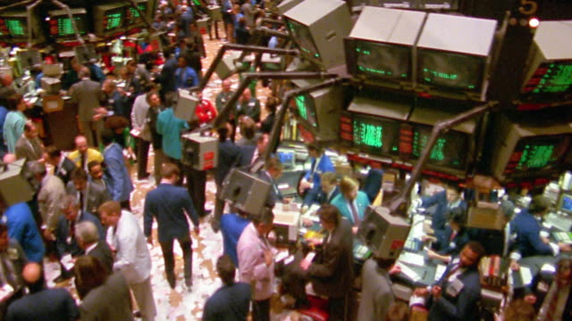high angle wide shot tilt down pan stockbrokers on busy trading floor of new york stock exchange / new york city - market trader stock videos & royalty-free footage