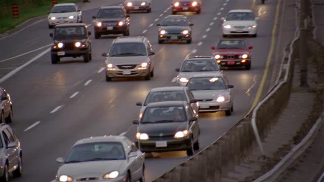 vidéos et rushes de high angle wide shot tilt down rush hour traffic on gardiner expressway and pedestrians crossing overpass at dusk / toronto - kelly mason videos
