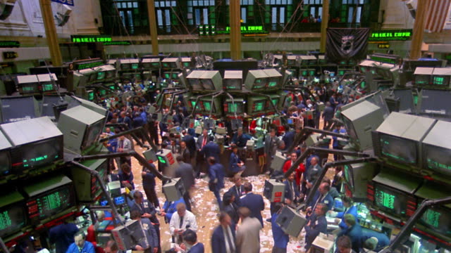 High angle wide shot tilt down time lapse stockbrokers on busy trading floor of New York Stock Exchange / New York City