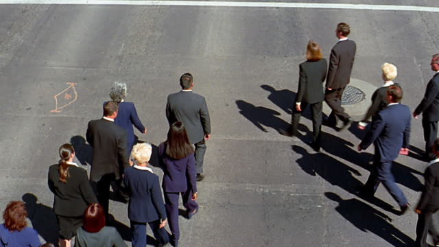 High angle wide shot tilt up 2 large groupd of business people converging on street