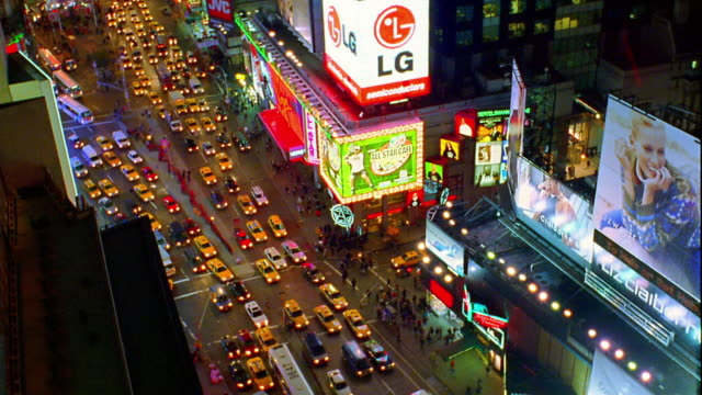 high angle wide shot tilt up from traffic on broadway and 7th avenue to buildings + signs in times square at night / new york city - 1998 stock-videos und b-roll-filmmaterial