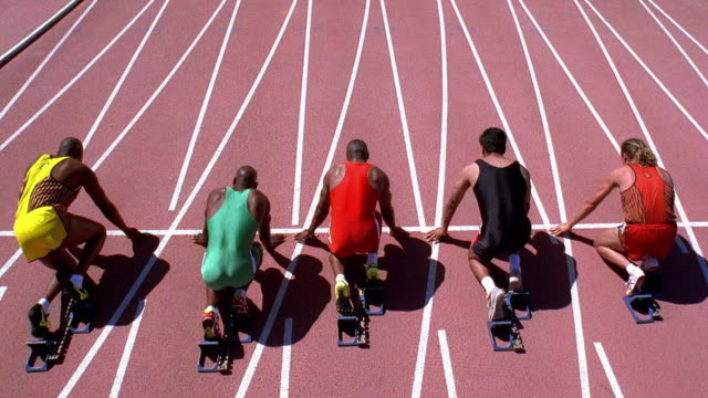 high angle wide shot tilt up male runners getting set on starting blocks and beginning race - blocco di partenza per l'atletica video stock e b–roll