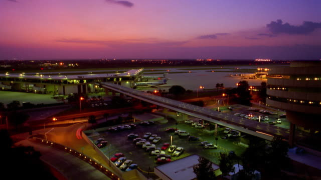 high angle wide shot time lapse airplanes taxiing on runways at tampa airport with traffic in foreground at dusk / florida - tampa stock videos & royalty-free footage