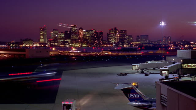 high angle wide shot time lapse airplanes taxiing to terminals and runways with city skyline in background / boston - boston massachusetts stock videos & royalty-free footage