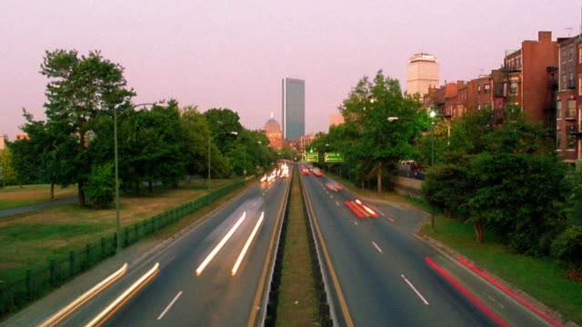 vídeos de stock e filmes b-roll de high angle wide shot time lapse cars on storrow drive with prudential tower and hancock tower in background / dusk to night / boston - back bay boston