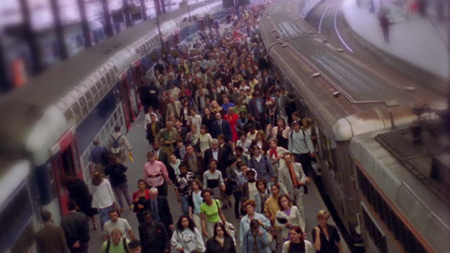 CANTED high angle wide shot time lapse commuters exiting trains + platform at rush hour / Gare St Lazare, Paris, France