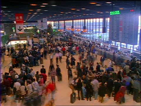high angle wide shot time lapse crowd of people in main room of narita airport, tokyo / japan - 1990~1999年点の映像素材/bロール