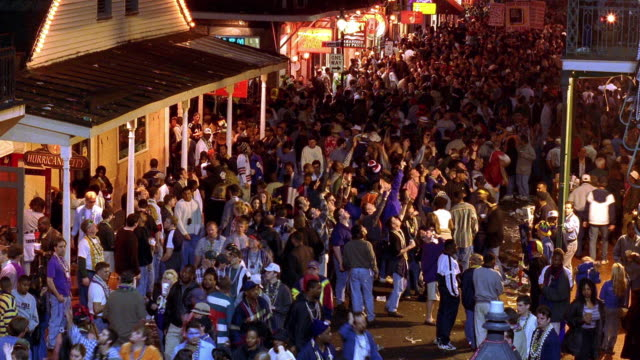 high angle wide shot time lapse crowds of people celebrating mardi gras on bourbon street / new orleans, louisiana - mardi gras stock videos and b-roll footage