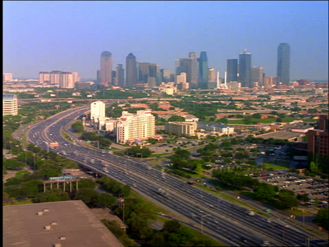 high angle wide shot time lapse Dallas skyline with highway traffic in foreground