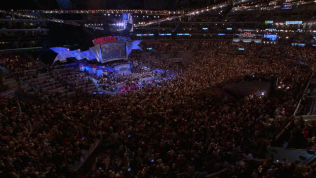 high angle wide shot time lapse Democratic National Convention with large crowd leaving arena after event / Los Angeles, CA