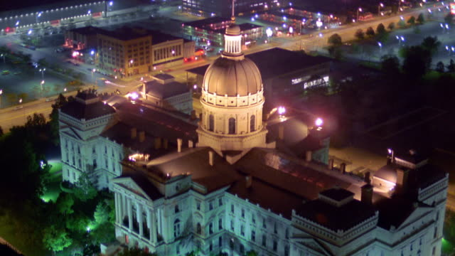 High angle wide shot time lapse Indianapolis Capitol Building with traffic on streets in background at night / Indiana