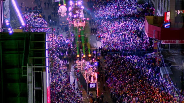 High angle wide shot time lapse large crowds and searchlights in Times Square at night on New Year's Eve / New York City