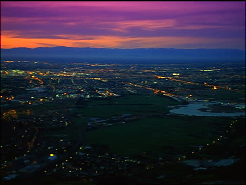 high angle wide shot PAN time lapse lights in city in valley at dusk / Christchurch, South Island / New Zealand