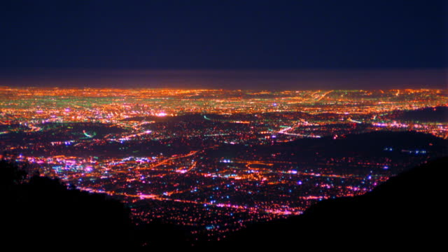 High angle wide shot time lapse lights of Los Angeles at night with trails from planes flying overhead / California
