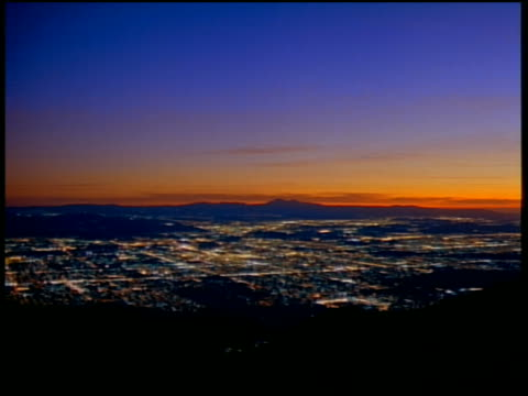High angle wide shot time lapse lights of San Fernando Valley with sunset and mountains in background / Los Angeles, California