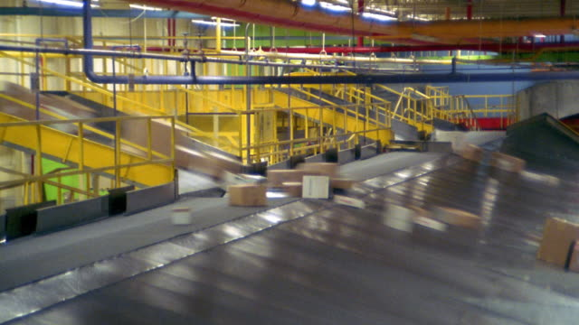 High angle wide shot time lapse packages being sorted on large conveyor machine in warehouse / Memphis, Tennessee