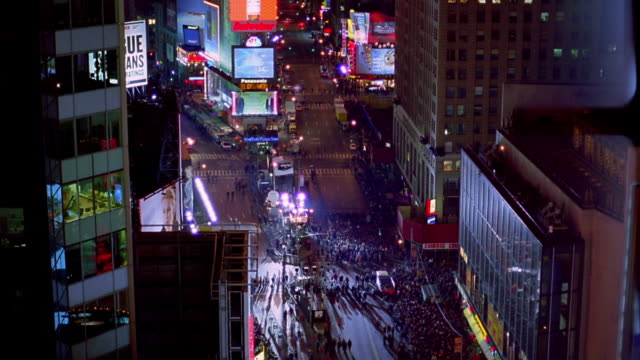 high angle wide shot time lapse traffic and growing crowds of people in times square at night on new year's eve / new york city - 1分以上点の映像素材/bロール