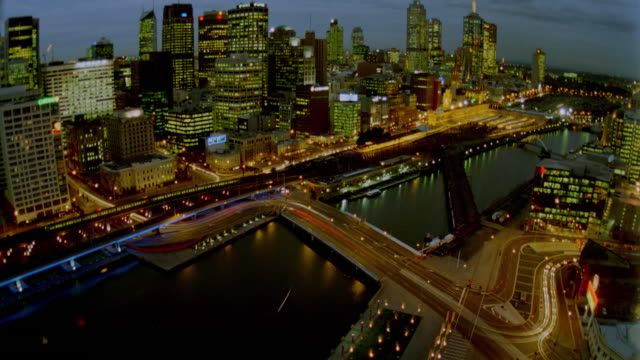 high angle wide shot time lapse traffic in front of melbourne skyline / dusk to night / victoria, australia - 1999 stock videos & royalty-free footage