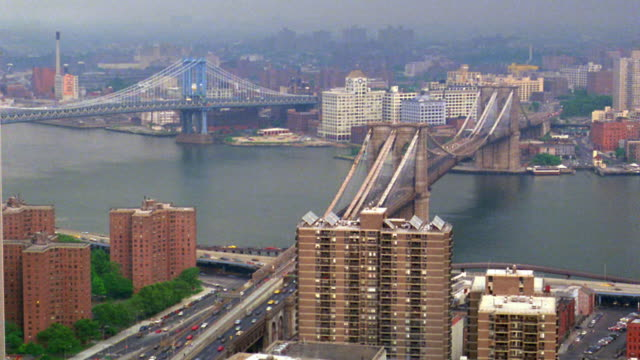 High angle wide shot time lapse traffic on Brooklyn Bridge with boats on East River and Manhattan Bridge in background / New York City