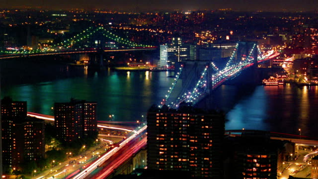 High angle wide shot time lapse traffic on Brooklyn Bridge with boats on East River and Manhattan Bridge in background at night / NYC