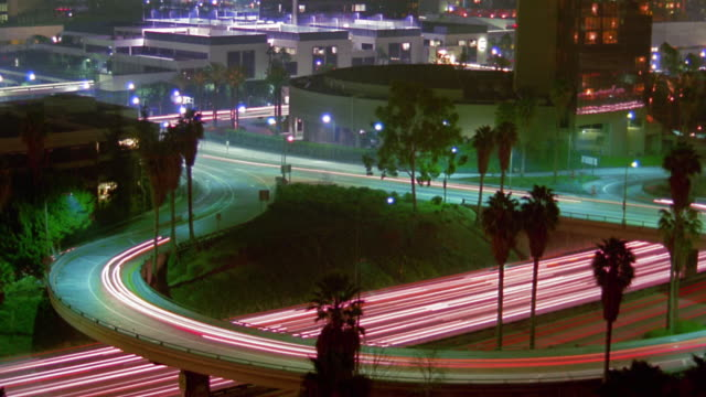 vídeos y material grabado en eventos de stock de high angle wide shot time lapse traffic on highway and overpass with buildings in background at night / los angeles, california - 1985