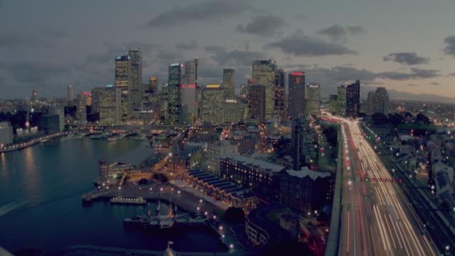 high angle wide shot time lapse traffic on highway + sydney city skyline at dusk / sydney, australia - zweispurige strecke stock-videos und b-roll-filmmaterial