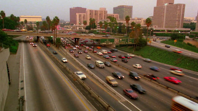 High angle wide shot time lapse traffic on highway with buildings in background / day to night / Los Angeles, California