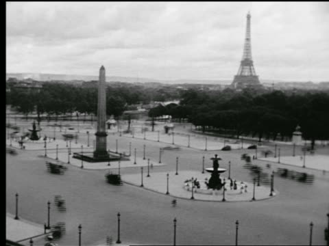 B/W 1927 high angle wide shot time lapse traffic + people in Place de la Concorde with Obelisk / Eiffel Tower in background / Paris