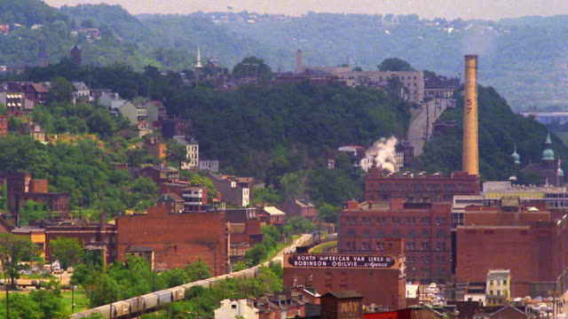 high angle wide shot time lapse train passing factory with buildings on hillside in background / pittsburgh, pennsylvania - pittsburgh video stock e b–roll