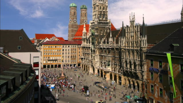 High angle wide shot time lapse view of people walking around Marienplatz from the Toy Museum / Munich, Germany