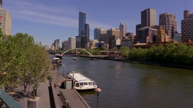 high angle wide shot tourboat moored on yarra waterfront with southbank footbridge and skyline in background/ melbourne, australia - tourboat stock videos & royalty-free footage