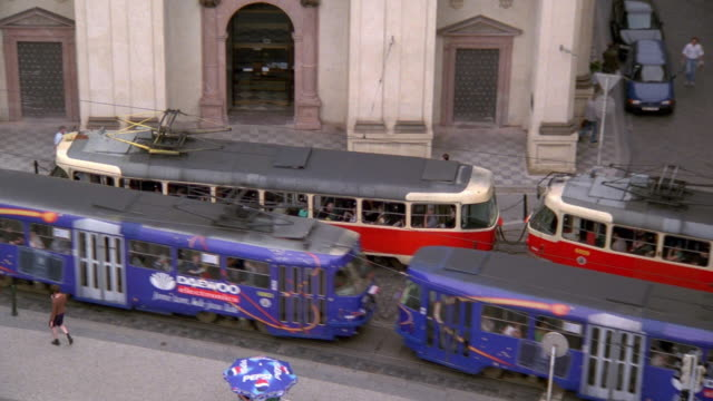 stockvideo's en b-roll-footage met high angle wide shot tracking shot trams and traffic on street at knights of the cross square / prague old town - praag oudestadsplein
