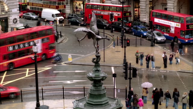 vídeos de stock, filmes e b-roll de high angle wide shot traffic and pedestrians around eros statue in piccadilly circus/ london - cupido