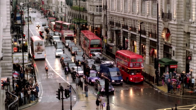 high angle wide shot traffic and pedestrians at intersection in piccadilly circus/ london - rain stock videos & royalty-free footage