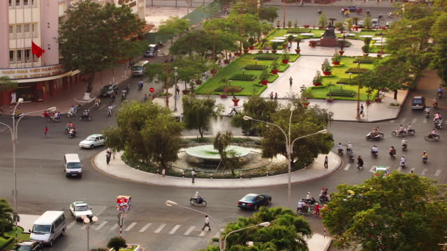 High angle wide shot traffic around roundabout in front of Rex Hotel / Ho Chi Minh City, Vietnam