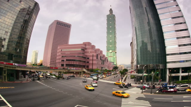 high angle wide shot traffic moving along xinyi road in front of the convention center / taipei taiwan - taipei 101 stock videos & royalty-free footage