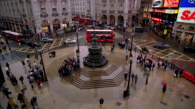 high angle wide shot traffic moving around eros statue in piccadilly circus/ london - piccadilly stock videos and b-roll footage