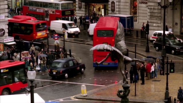 vídeos de stock, filmes e b-roll de high angle wide shot traffic moving past eros statue in piccadilly circus/ london - cupido