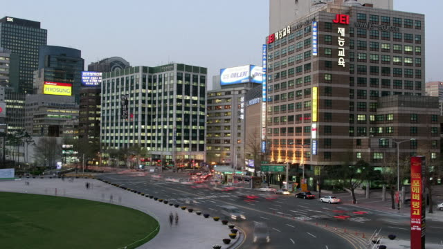high angle wide shot traffic moving through downtown seoul near seoul plaza as night falls / seoul, south korea - bus billboard stock videos & royalty-free footage