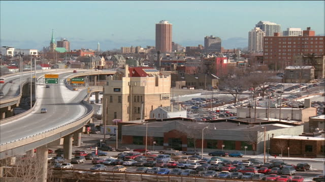 high angle wide shot traffic on elevated highway / pan parking lots, buildings and streets / milwaukee, wisconsin - 1995 stock videos & royalty-free footage