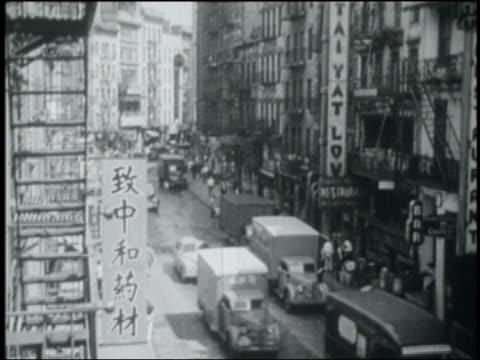 vídeos de stock, filmes e b-roll de b/w 1949 high angle wide shot trucks + people on city street in chinatown / nyc - bairro chinês